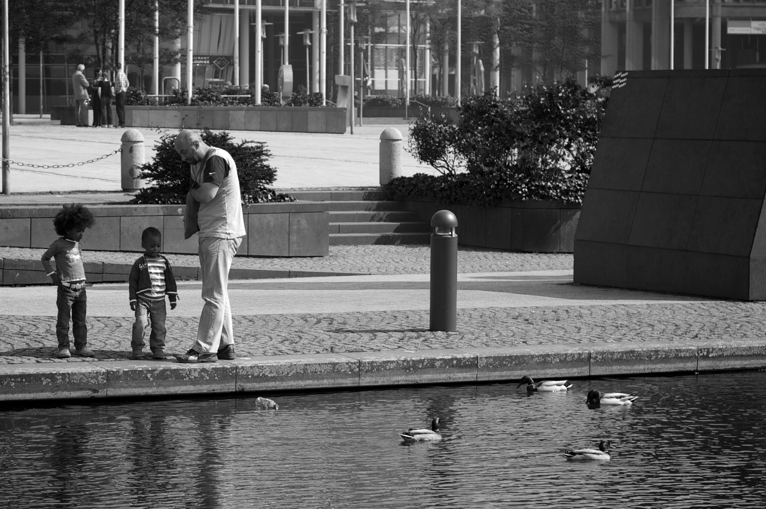 Probably a father with his children, watching and feeding ducks.