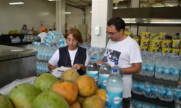 La doctora Mirelly Gómez y nuestro compañero Michael Erbozo supervisan la recepción de los alimentos