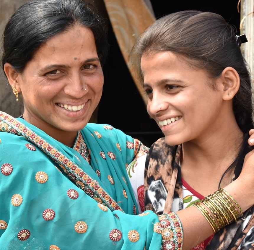 madre e hijas abrazadas sonrriendo