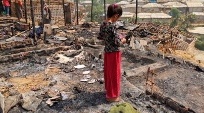 Niña de pie mirando el incendio Cox Bazar
